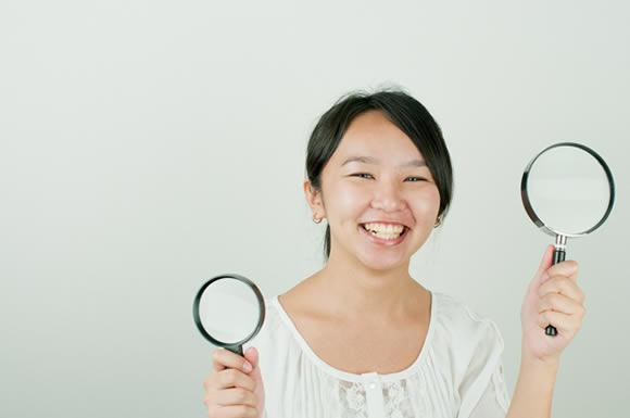 虫眼鏡をかざす女性