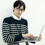パソコンをいじるメガネの男性