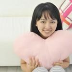ハートの枕を抱きしめる女性