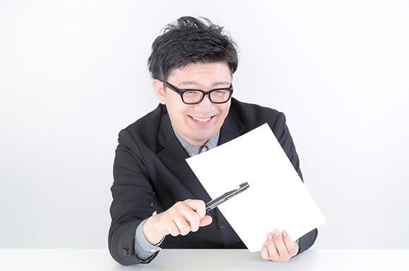 紙にペンを突きつける男性